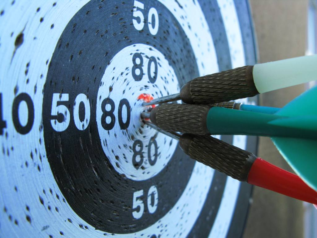 Dartboard showing darts on target that have hit the bulls eye